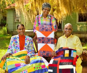 Women of Gee's Bend Holding Quilts